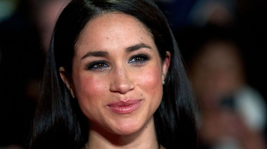 """(FILES) This file photo taken on November 11, 2013 shows  US actress Meghan Markle as she poses for pictures on the red carpet upon arrival for the world premier of the film """"The Hunger Games: Catching Fire"""" in Leicester Square, central London. Britain's Prince Harry confirmed on November 8, 2016, that he is dating US actress Meghan Markle as he hit out at the """"wave of abuse and harassment"""" she has suffered in recent weeks. In an unprecedented statement from Kensington Palace, the prince, 32, urged media organisations to refrain from """"further damage"""" as he blasted the smears and """"racial undertones"""" appearing in newspaper articles. / AFP / Andrew Cowie"""